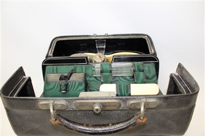Lot 3064-Finnigan's leather portmanteau with four silver top bottles