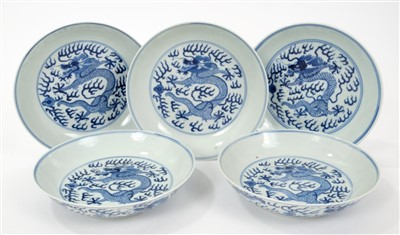 Lot 14-Set five 19th century Chinese blue and white saucer dishes with painted dragon chasing pearl decoration to front and back and six character Guangxu marks and probably of the period 16.5cm