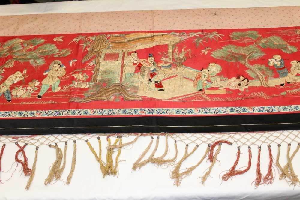 Lot 3055-Chinese embroidered red silk banner. Silk satin stitch with crouched outlines. Garden scene with pagodas, ducks etc.