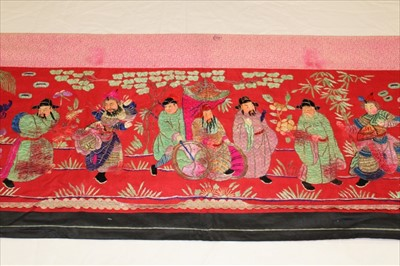 Lot 3054-Chinese embroidered red silk banner. Silk satin stitch with crouched outlines, figures have painted silk faces, Wiseman in sedan chair, dancers and deities in garden scene. Printed cotton lining