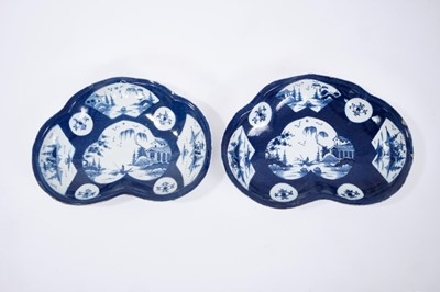 Lot 23-Pair of Bow blue and white kidney-shaped dishes, circa 1760, the central panel painted with a fisherman, on a powder blue ground with further panels