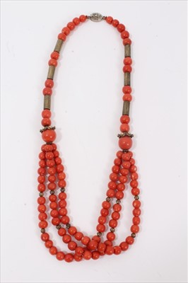 Lot 7-Old Chinese coral necklace with spherical polished beads and metal spacers, terminating with three strands of beads and a silver clasp