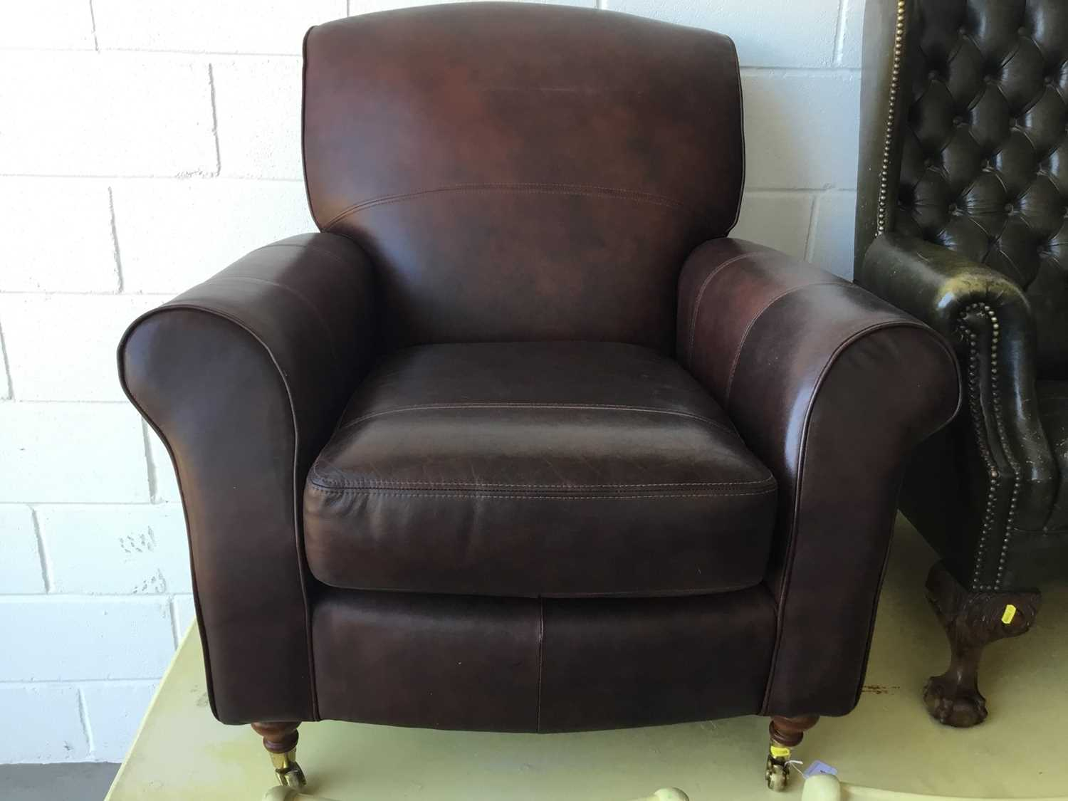 Lot 15-Good quality contemporary brown leather arm chair by Marks & Spencer, on turned feet with brass castors, 93cm in overall height
