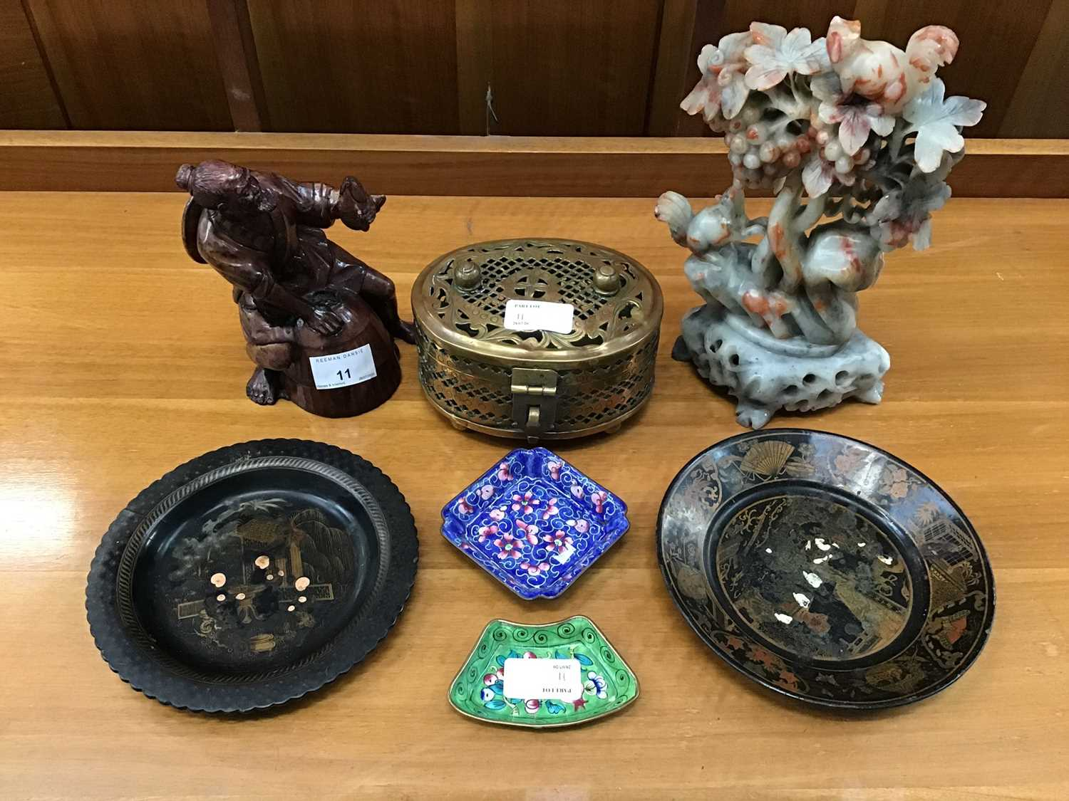 Lot 11-Oriental soapstone and resin carved figures, together with two lacquered papier-mâché dishes and other oriental items