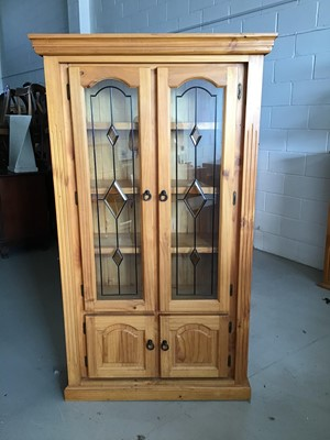 Lot 22 - Contemporary stained pine bookcase with two leaded glazed doors above enclosing three fixed shelves and two panelled doors below H180cm W104cm D37cm