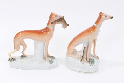Lot 24-Two Victorian Staffordshire figures of greyhounds, the largest measuring 21cm height