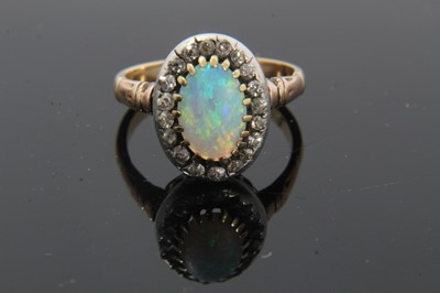 Lot 21-Antique opal and diamond cluster ring with an oval cabochon opal surrounded by nineteen old cut diamonds in silver collet setting with pierced gold gallery on gold shank