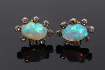 Lot 22-Pair of antique opal and diamond earrings, each with a opal cabochon surrounded by rose cut diamonds in silver and gold setting