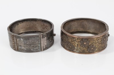 Lot 20-Two Victorian silver hinged bangles, one with applied and textured floral design, Birmingham 1883, the other with engraved scenes depicting various boats in coastal bays
