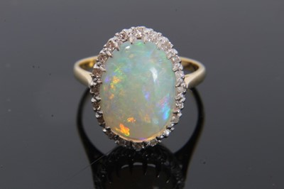 Lot 24-Opal and diamond cluster ring with an oval cabochon opal surrounded by 20 single cut diamonds on 18ct gold shank