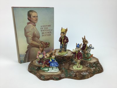 Lot 183 - Five Royal Doulton Bunnykins figures - Mr Bunnykins, Buntie, Rise and Shine, Sleigh Ride and Tally Ho, Beswick stand and a book - A History Of The Writings of Beatrix Potter