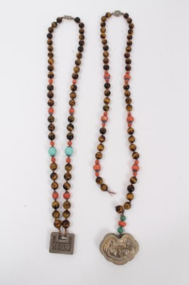 Lot 8 - Two Chinese tiger's eye and coral bead necklaces with white metal panel pendants