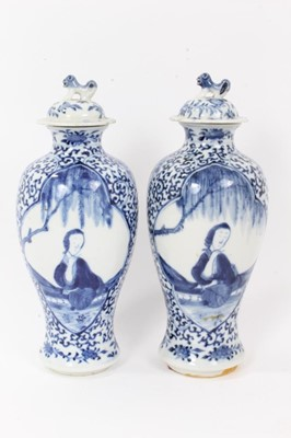 Lot 8 - Pair 19th century Chinese blue and white porcelain baluster vases and cover, decorated with figural panels on a foliate patterned ground