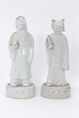 Lot 42 - Good pair of antique Chinese Qing period blanc de chine figures, the female figure carrying a fly whisk, the male figure carrying a piece of fruit, both standing on bases with stylised waves, 21.5c...