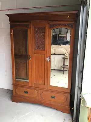 Lot 10 - Art Nouveau mahogany wardrobe, with moulded cornice and twin mirrored doors between relief carved foliate panel and two drawers below on plinth base, 148cm wide x 54cm deep x 201cm high