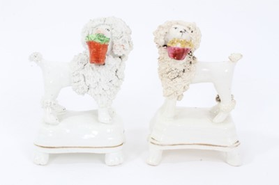 Lot 29 - Two Staffordshire porcelain poodles with baskets, c.1840, highlighted in enamels and gilt, 9.5cm height