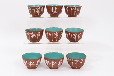 Lot 61 - Set of nine Chinese Yixing pottery tea bowls, painted with calligraphy, enamelled blue inside and on the bases, each approximately 7cm diameter x 4.5cm height