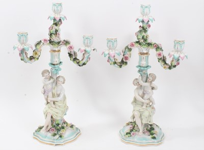 Lot 79 - Pair of Dresden figural porcelain candelabra, with three branch section fitting on to a central column, with floral encrusted decoration, marks to bases, total height 47cm