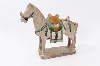Lot 87 - Chinese Tang-style pottery figure of a horse, partially glazed in yellow and green, standing on a rectangular base, 28cm height