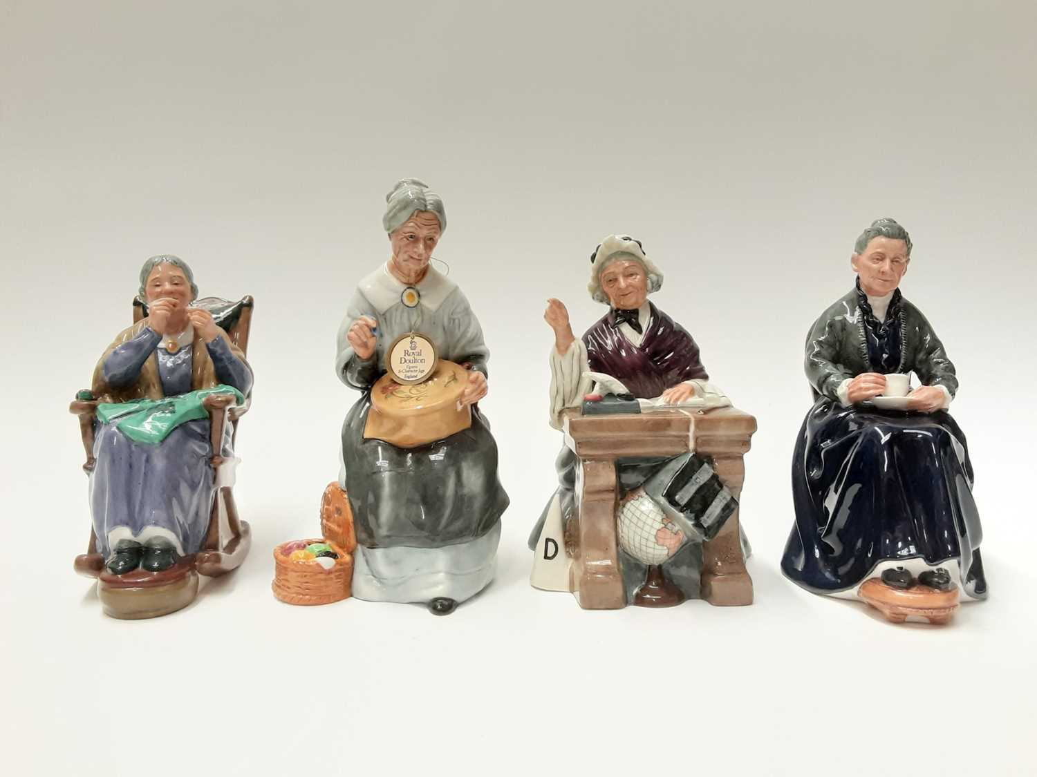 Lot 58 - Four Royal Doulton figures - The Cup Of Tea HN2322, Schoolmarm HN2223, A Stitch In Time HN2352 and Embroidering HN2855