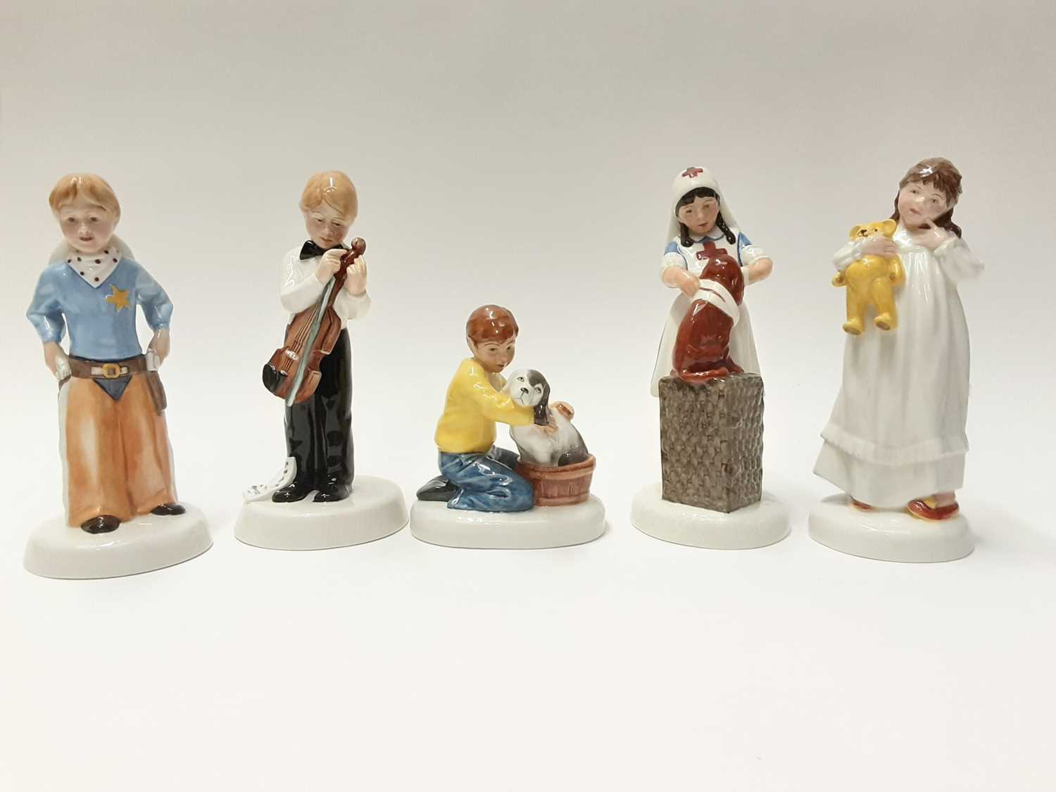 Lot 63 - Five Royal Doulton Childhood Days figures - Please Keep Still HN2967, I'm Nearly Ready HN2976, Stick 'Em Up HN2981, And So To Bed HN2966 and It Won't Hurt HN2963