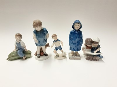 Lot 149 - Five Royal Copenhagen porcelain figures including child in raincoat, boy and girl reading and boy with football