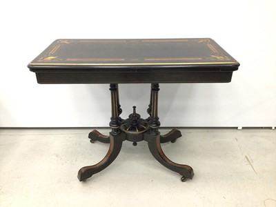 Lot 62 - Victorian ebonised and amboyna inlaid card table, with inlaid fold over rounded rectangular top, well below, raised on four columns with gilt fluted ornament and spread supports on castors, united...