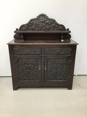 Lot 69 - Impressive 19th century Arts and Crafts carved oak Chiffonier, with arched gallery and shelf back raised on dragon supports, having two drawers and cupboards below on styles, allover relief carved...