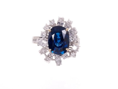Lot 488 - Sapphire and diamond cluster cocktail ring with an oval mixed blue sapphire measuring approximately 11.75mm x 8.75mm x 5.75mm, surrounded by an asymmetric border of brilliant cut and marquise cut d...