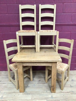 Lot 929 - Contemporary light oak dining table and four matching ladder back chairs with rush seats