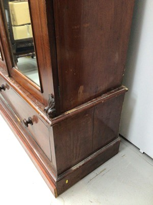Lot 11 - Victorian mahogany double wardrobe with two arched mirror doors and drawer below, 127cm wide x 57cm deep x 211cm high