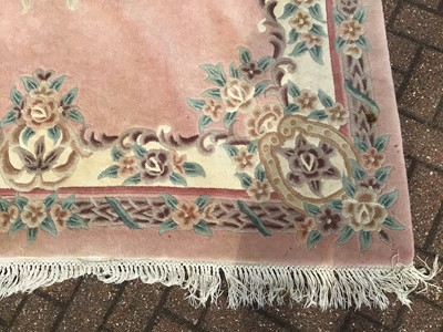 Lot 66 - Chinese wash rug with floral decoration on peach ground 274cm x 186cm with a smaller round rug of similar description 134cm