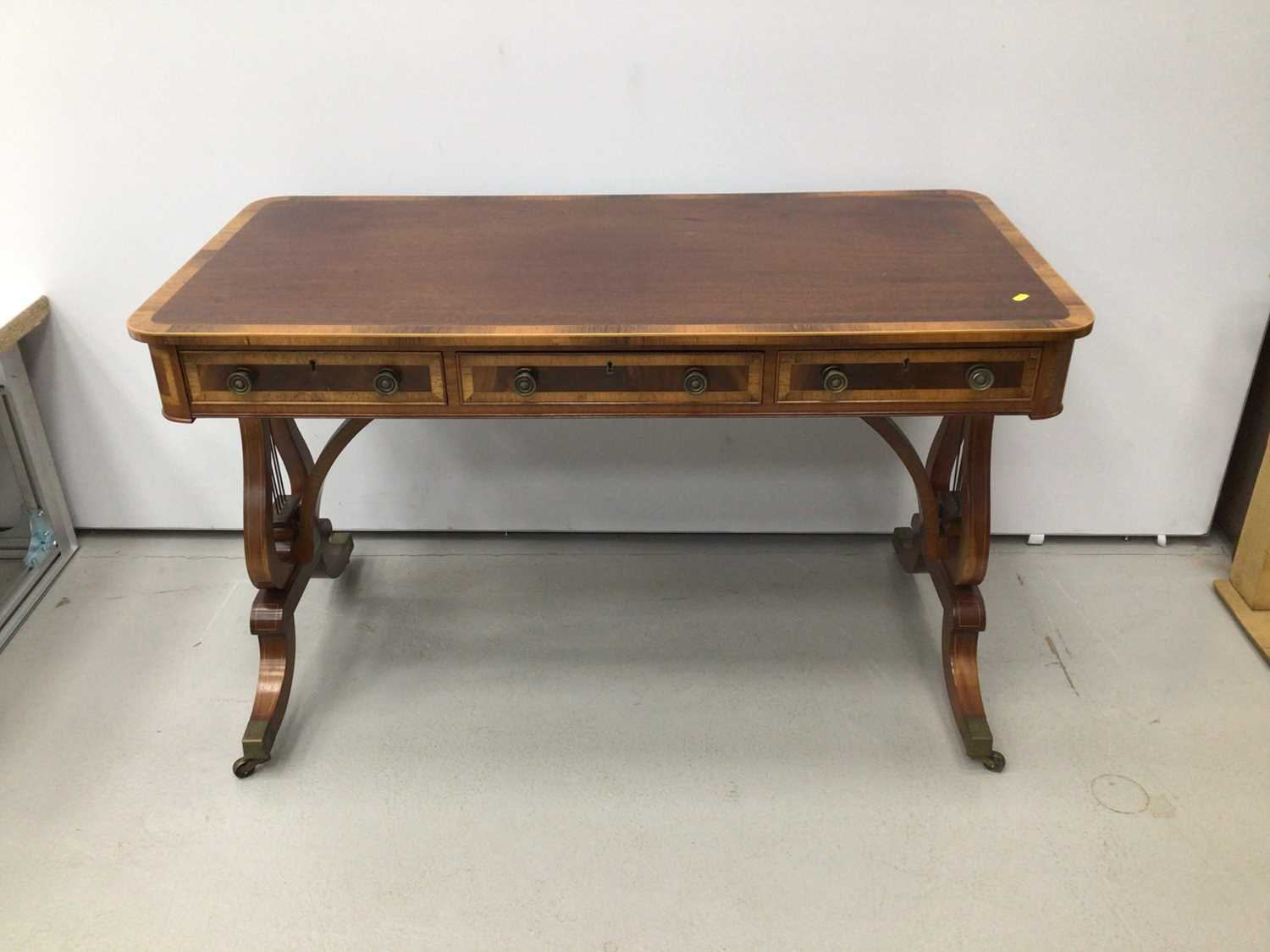 Lot 72 - Good quality Redman and Hales Georgian style mahogany writing table with cross banded decoration and three draws on lyre end standards 122cm wide x 61cm deep x 74.5cm high