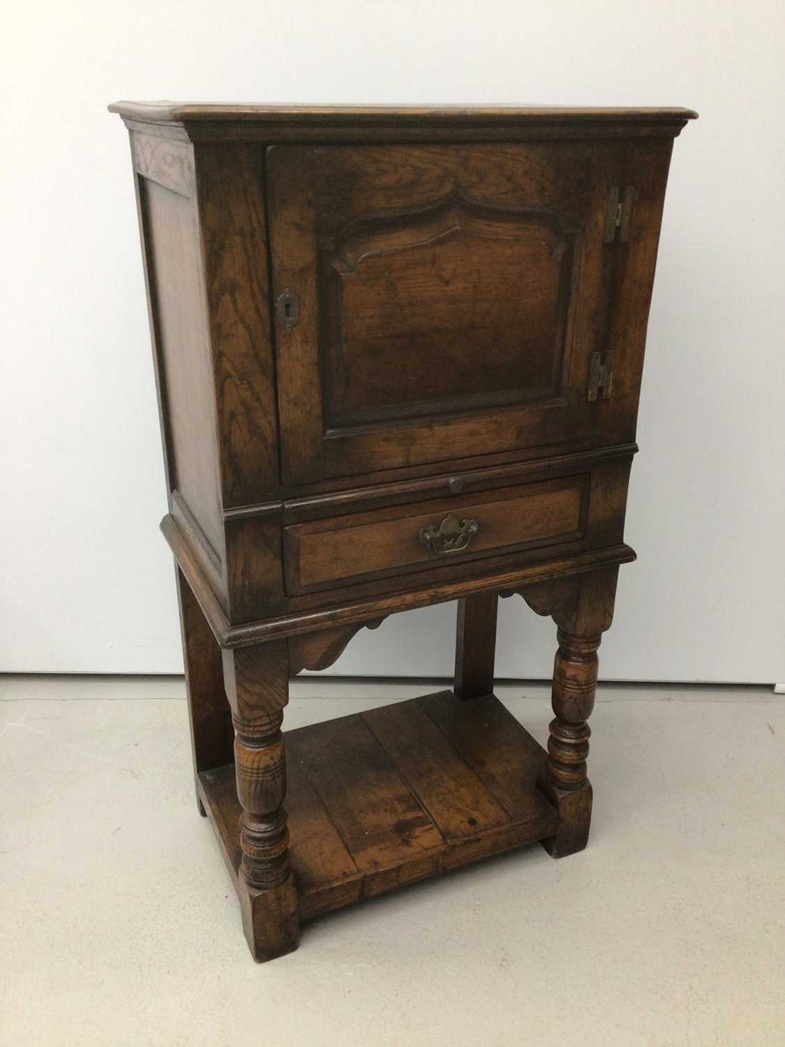 Lot 90 - Antique style oak cupboard with panelled door, draw below on turned front supports with under tier 62cm wide x 41cm deep x 114cm high