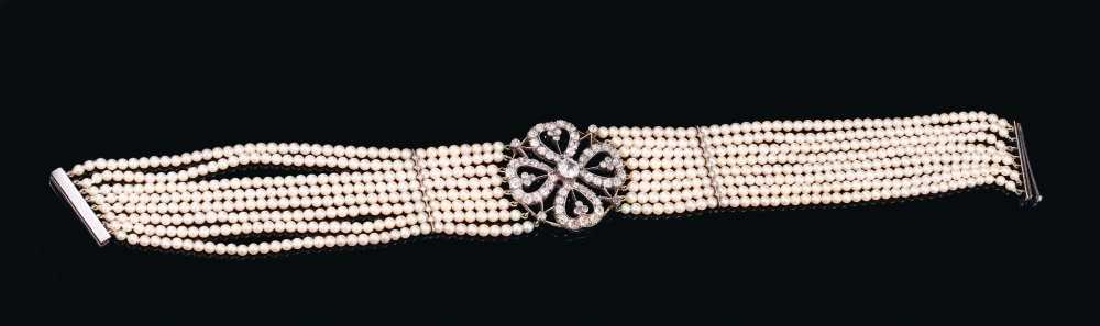 Lot 525 - Diamond and cultured pearl choker necklace, the diamond openwork plaque with a four-leaf clover design centred with a principal old cut diamond estimated to weigh approximately 1.2cts, with old cut...