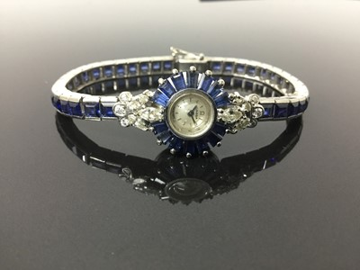 Lot 533 - 1950s/1960s ladies Omega diamond and sapphire cocktail wristwatch, the circular dial with concealed winding crown, tapered baguette cut sapphires and diamond lugs with marquise and brilliant cut di...