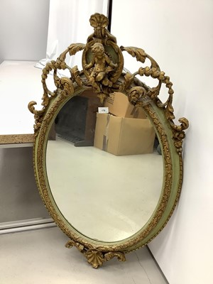 Lot 170 - Oval wall mirror in green and gilt frame with cherub mount, 100cm x 61cm