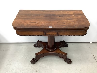 Lot 174 - 19th century rosewood card table with foldover revolving top on turned column and quatrefoil base with carved paw feet, 90.5cm wide x 14.5cm high