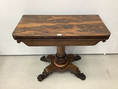 Lot 180 - 19th century rosewood card table with foldover revolving top on turned column and quatrefoil base with carved paw feet, 92cm wide x 74.5cm high