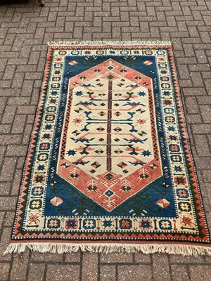 Lot 186 - Eastern rug with geometric decoration on red, blue, greem and cream ground, 188cm x 123cm