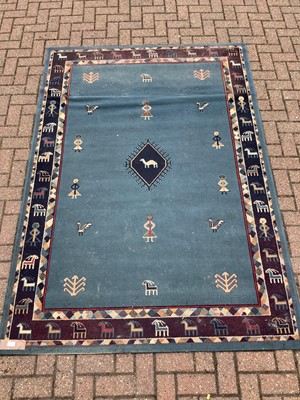 Lot 187 - Old rug decorated with figures and animals on blue ground  228cm x 160cm