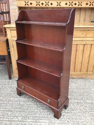 Lot 918 - Reproduction mahogany waterfall front open bookcase with single drawer, on bracket feet