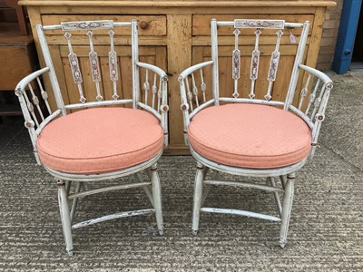 Lot 919 - Pair of painted open elbow chairs with decorative shaped backs, caned seats with cushions, on shaped legs joined by stretchers