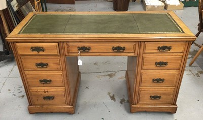 Lot 854 - Late 19th / early 20th century satin birch desk, with green leather top and nine drawers about the kneehole on plinth base and castors, 138cm wide x 67cm x 82cm high