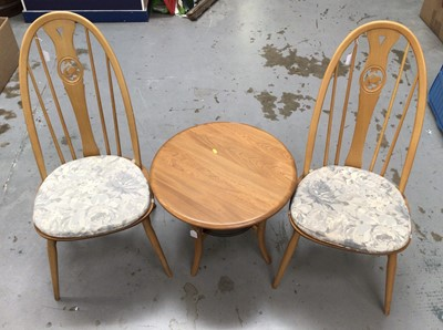 Lot 857 - Ercol two tier coffee table with circular top and glass undertier model number 1061, H47, W60cm together with a pair of Ercol swan back chairs