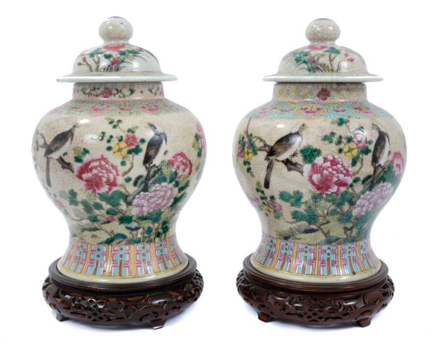 Lot 1 - Pair of Chinese famille rose porcelain crackle-glazed jars and covers with carved hardwood stands, approximately 26cm excluding stands.
