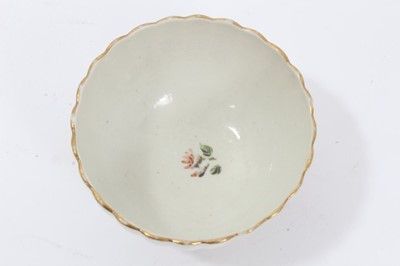 Lot 24 - Worcester fluted tea bowl and saucer, circa 1772, polychrome painted with flowers, with gilt rims, the saucer measuring 13.5cm diameter