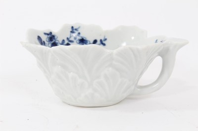Lot 54 - Worcester blue and white leaf moulded butter boat, circa 1755, decorated with floral sprays, painter's mark to bottom of handle, 8.5cm long