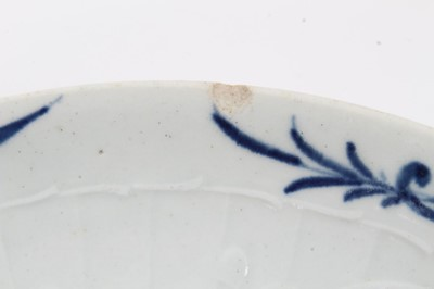 Lot 55 - Worcester blue and white strap-fluted saucer dish, circa 1756, decorated with scrollwork panels containing Chinese landscapes, and foliate patterned rim, 18.5cm diameter