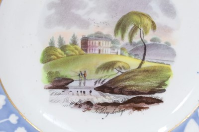Lot 56 - Pair of New Hall plates, circa 1815-20, with printed and coloured titled scenes, the edges with relief moulded foliate patterns on a blue ground, 20.5cm diameter